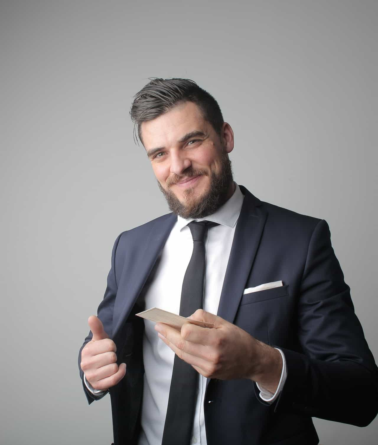Man in suit smiling offering business card